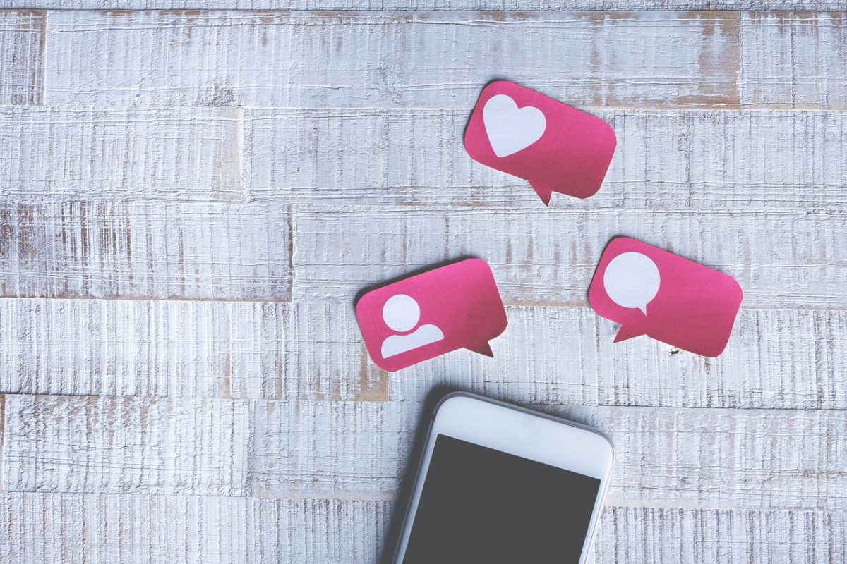 iPhone with social media hearts and symbols